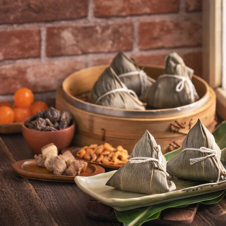 Rice dumpling - Chinese zongzi food in a steamer on wooden table with red brick wall, window background at home for Dragon Boat Festival concept, close up. Stock fotó