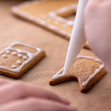 Young woman is decorating Christmas Gingerbread House cookies biscuit at home with frosting topping in icing bag, close up, lifestyle. Stock Photo