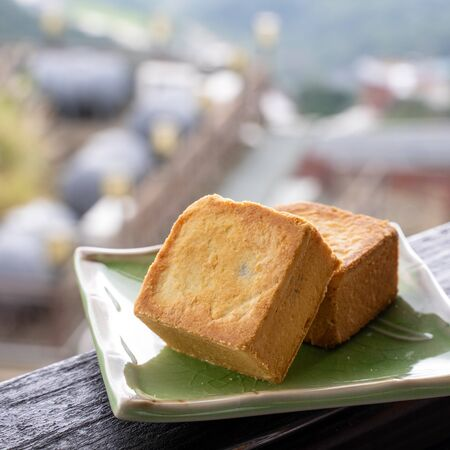 Delicious pineapple pastry in a plate for afternoon tea on wooden railing of a teahouse in Taiwan with beautiful landscape in background, close up.