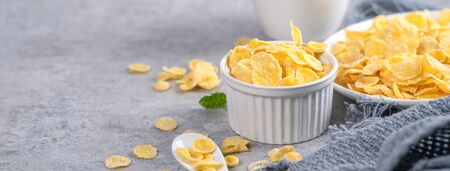 Corn flakes bowl sweeties with milk on gray cement background, close up, fresh and healthy breakbast design concept.