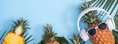 Funny pineapple wearing white headphone, concept of listening music, isolated on colored background with tropical palm leaves, top view, flat lay design. Banque d'images