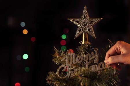 Christmas background concept- beautiful decor bauble hanging on the Christmas tree with sparkling light spot, blurry dark black background, copy space, close up.