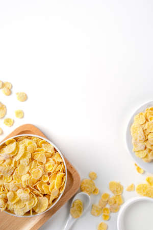 Corn flakes bowl sweeties with milk and orange on white background, top view, flat lay overhead layout, fresh and healthy breakfast design concept.
