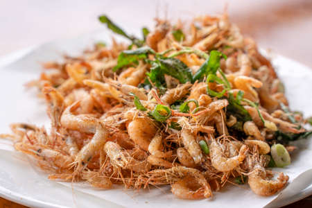 Salted fried crispy river shrimp prawn, Macrobrachium nipponense, in a white plate on wooden table, delicious Taiwanese street food, lifestyle.