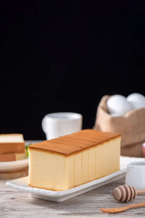 Castella (kasutera)-Delicious Japanese sliced sponge cake food on white plate over rustic wooden table, close up, healthy eating, copy space design.