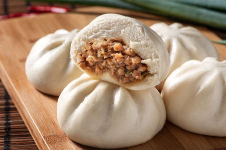 Delicious baozi, Chinese steamed meat bun is ready to eat on serving plate and steamer, close up, copy space product design concept. Stock Photo