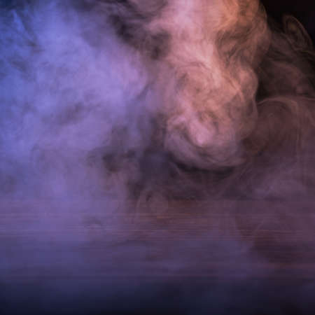Conceptual image of multi-colored smoke isolated on dark black background and wooden table. Banque d'images