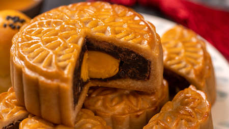 Tasty baked egg yolk pastry moon cake for Mid-Autumn Festival on black slate dark background. Chinese festive food concept, close up, copy space. Stockfoto