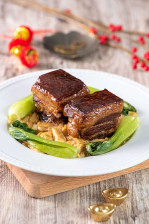 Dong Po Rou (Dongpo pork meat) in a beautiful blue plate with green broccoli vegetable, traditional festive food for Chinese new year cuisine meal, close up. Standard-Bild