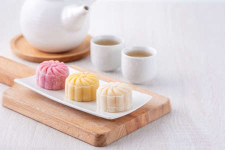 Colorful snow skin moon cake, sweet snowy mooncake, traditional savory dessert for Mid-Autumn Festival on bright wooden background, close up, lifestyle.