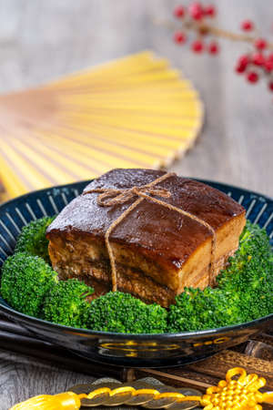 Dong Po Rou (Dongpo pork meat) in a beautiful blue plate with green broccoli vegetable
