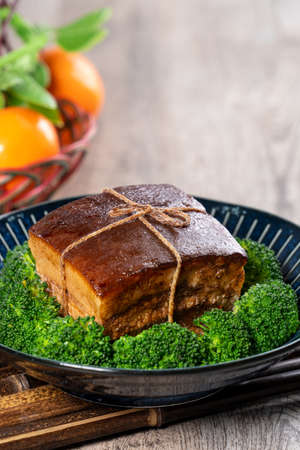 Dong Po Rou (Dongpo pork meat) in a beautiful blue plate with green broccoli vegetable Standard-Bild