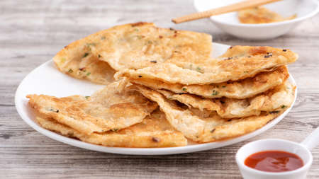 Taiwanese food-delicious flaky scallion pie pancakes on bright wooden table background, traditional snack in Taiwan, close up.