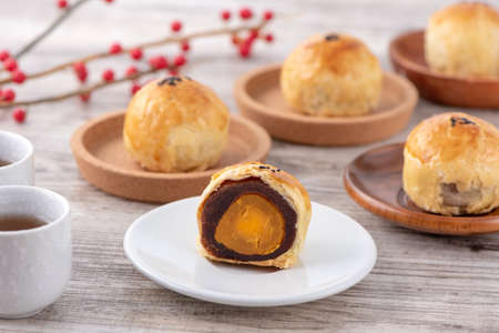 Moon cake yolk pastry, mooncake for Mid-Autumn Festival holiday, top view design concept on bright wooden table with copy space