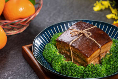 Dong Po Rou (Dongpo pork meat) in a beautiful plate with green broccoli vegetable, traditional festive food for Chinese new year cuisine meal, close up.