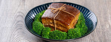 Dong Po Rou (Dongpo pork meat) in a plate with green vegetable, traditional festive food for Chinese lunar new year cuisine meal, close up. Banque d'images