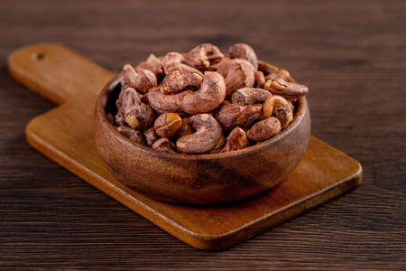 Cashew nuts with peel in a wooden bowl on wooden tray and table background, healthy raw food plate. Reklamní fotografie