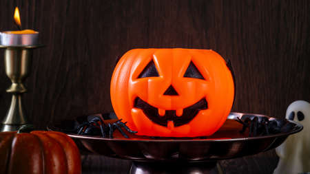 Spooky Halloween decor, horror festival concept, pumpkin lantern with candlestick.