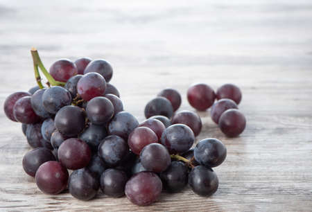 Delicious bunch of grapes fruit on a plate over wooden table background. Reklamní fotografie