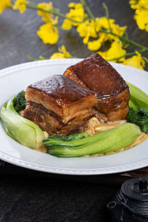 Dong Po Rou (Dongpo pork meat) in a beautiful plate with green vegetable, traditional festive food for Chinese new year cuisine meal, close up.