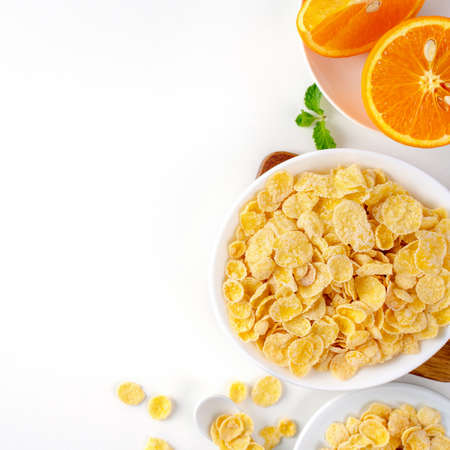 Top view of corn flakes bowl sweeties with milk and orange on white background, flat lay overhead layout, fresh and healthy breakfast design concept.