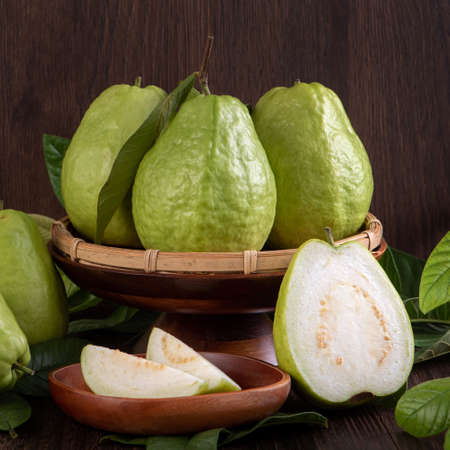 Close up of delicious beautiful guava set with fresh green leaves isolated on dark wooden table background. 免版税图像