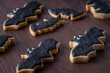 Close up of decorating cute Halloween bat gingerbread sugar cookies with frosting icing cream topping bag. 免版税图像