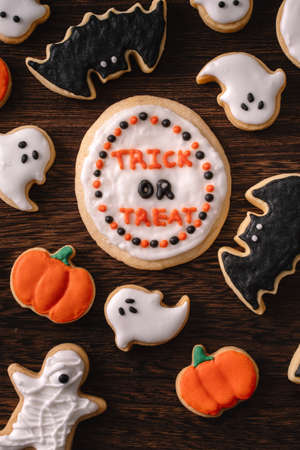 Top view of Halloween festive decorated icing gingerbread sugar cookies with copy space and flat lay layout.