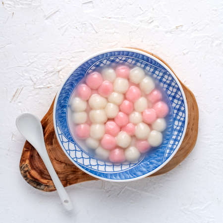 Top view of red and white tangyuan (tang yuan, glutinous rice dumpling balls) in blue bowl on white background for Winter solstice festival food. Stock Photo