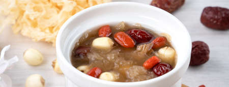 Close up of traditional Chinese sweet snow white fungus soup with lotus seed, red dates (jujube) and wolfberry (goji, gojiberry) on white background.