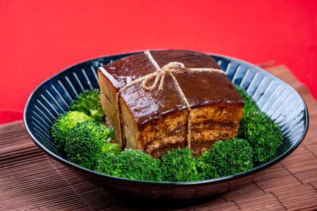 Dong Po Rou (Dongpo pork meat) in a beautiful blue plate with green broccoli vegetable, traditional festive food for Chinese new year cuisine meal, close up.