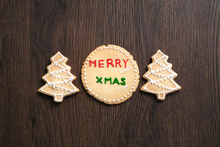 Top view of decorated Christmas tree gingerbread cookie on wooden table background with copy space, concept of holiday celebration.