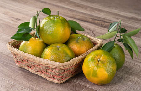 Fresh ripe tangerine mandarin orange in a box with fresh leaves on wooden table background harvest concept.