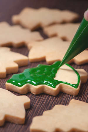 Close up of drawing gingerbread Christmas tree sugar cookie on wooden table background with green icing, concept of holiday celebration. Stock Photo