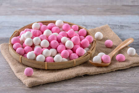 Raw red and white tangyuan glutinous rice dumpling balls on wooden table background for Winter solstice festival food.