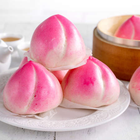 Pink Chinese peach birthday bun food named Longevity peach shoutao on white table background. 版權商用圖片