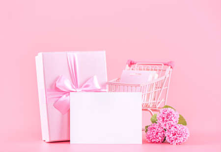 Mother's Day holiday gift design concept, pink carnation flower bouquet with wrapped gift box isolated on pink background, copy space. Stock Photo