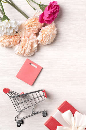 Design concept of Mother's Day greeting with carnation flower, holiday gift idea and shopping cart on wooden background.