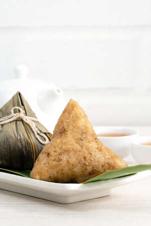 Zongzi. Rice dumpling for Chinese traditional Dragon Boat Festival (Duanwu Festival) on bright wooden table background.
