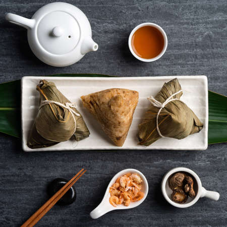 Zongzi. Rice dumpling top view design concept for Chinese traditional Dragon Boat Festival (Duanwu Festival) over dark black slate background.