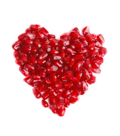Pomegranate in the form of heart on a white background photo