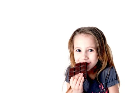 Cute blond smiling little girl eating chocolate tablet with tricky expression, isolated on white, space for text