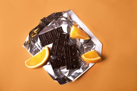 Chocolate bar broken in pieces with segments of an orange on foil insert on yellow background