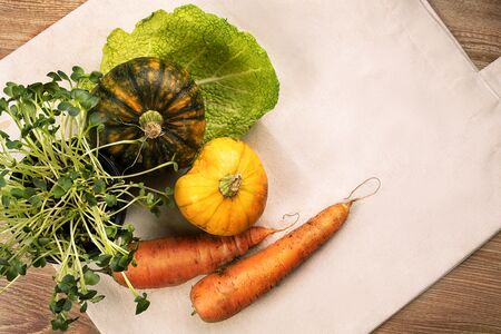 Fresh vegetables, pumpkins, cabbage leaf with green grass in pot, flatlay on eco bag and wooden background table