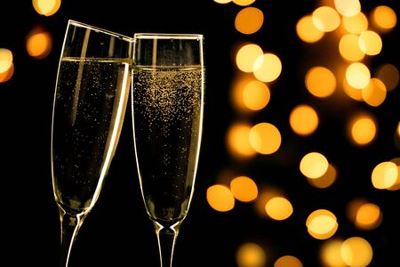 Two champagne glasses toasting on black background with bokeh lights, happy new year