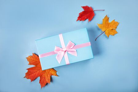 Blue gift box with atlas pink ribbon on blue background with bright autumn leaves