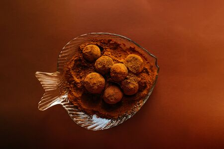 Chocolate balls with cocoa powder spread over fish shape transparent plate