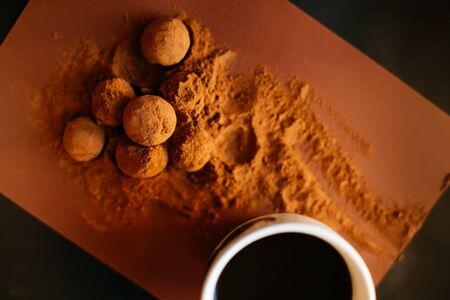 Chocolate balls with cocoa powder and coffee mug