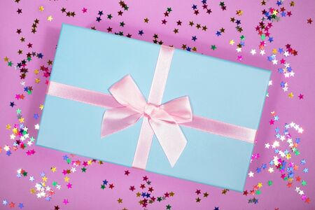 Beautiful gift box with atlas ribbon on purple background with sparkling stars, festive concept