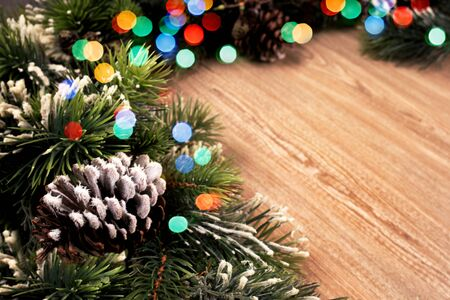 Christmas tree green branch with pine and colourful lignts on wooden background